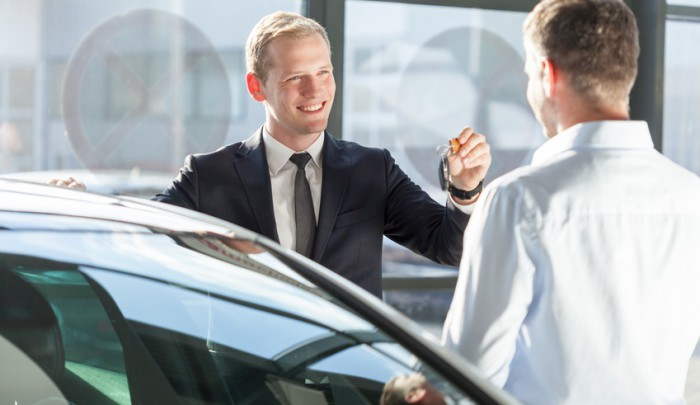 Smiling salesman giving car key to new owner